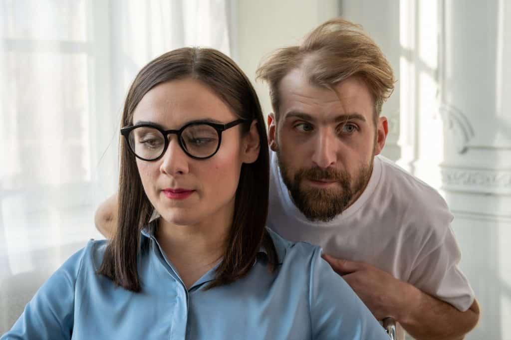 Homem falando algo pelo ombro de uma mulher, que olha para o lado.