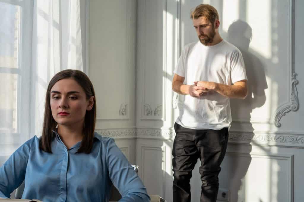 Mulher brava sentada na cadeira enquanto o homem está de pé mais ao fundo aflito