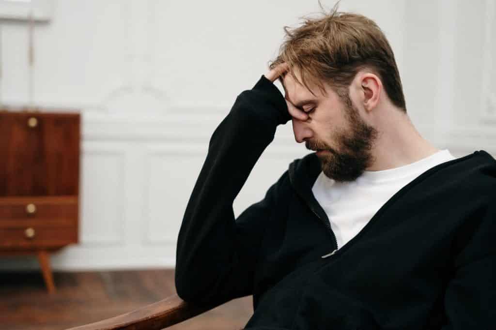 Homem sentado com uma das mãos na cabeça pensativo