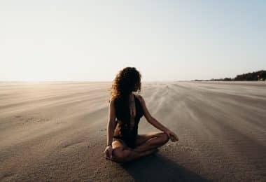 Mulher sentada em areia meditando