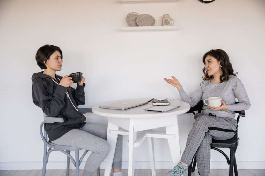 Duas mulheres sentadas à mesa, conversando.