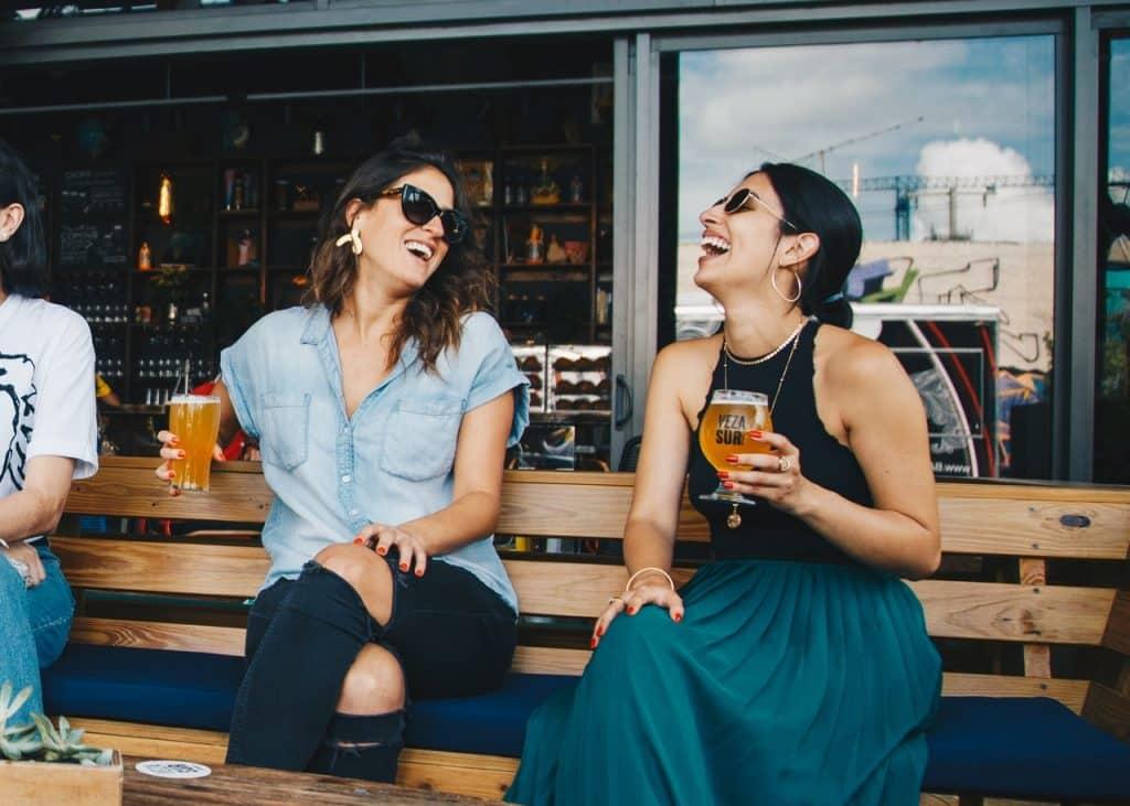 Duas mulheres sentadas, segurando copos de cerveja e rindo.