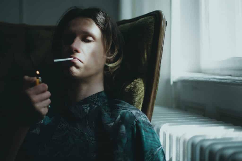Homem com olhar despreocupado acendendo um cigarro.