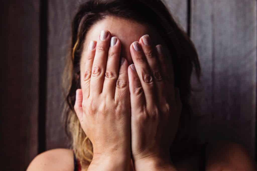 Mulher com as mãos no rosto