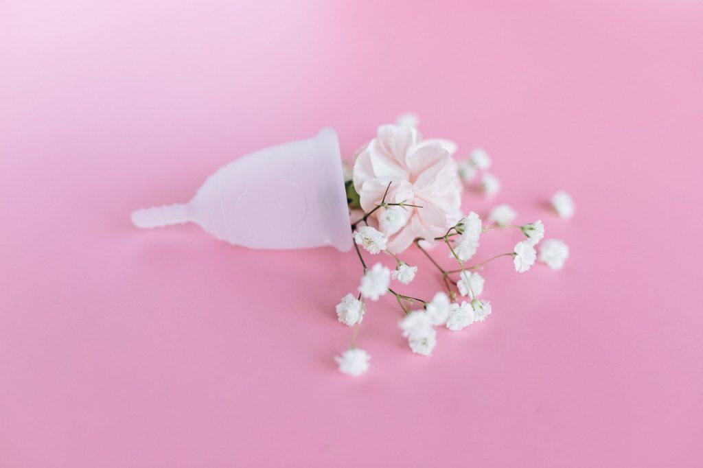 Um coletor menstrual com flores sob o fundo rosa.
