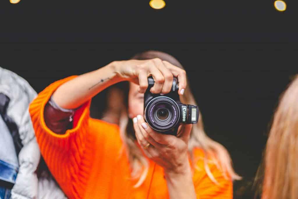 Mulher fotografando com uma câmera fotográfica