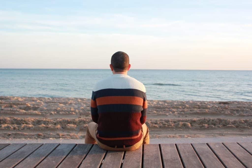 Homem sentado na beira da praia, visto de costas.