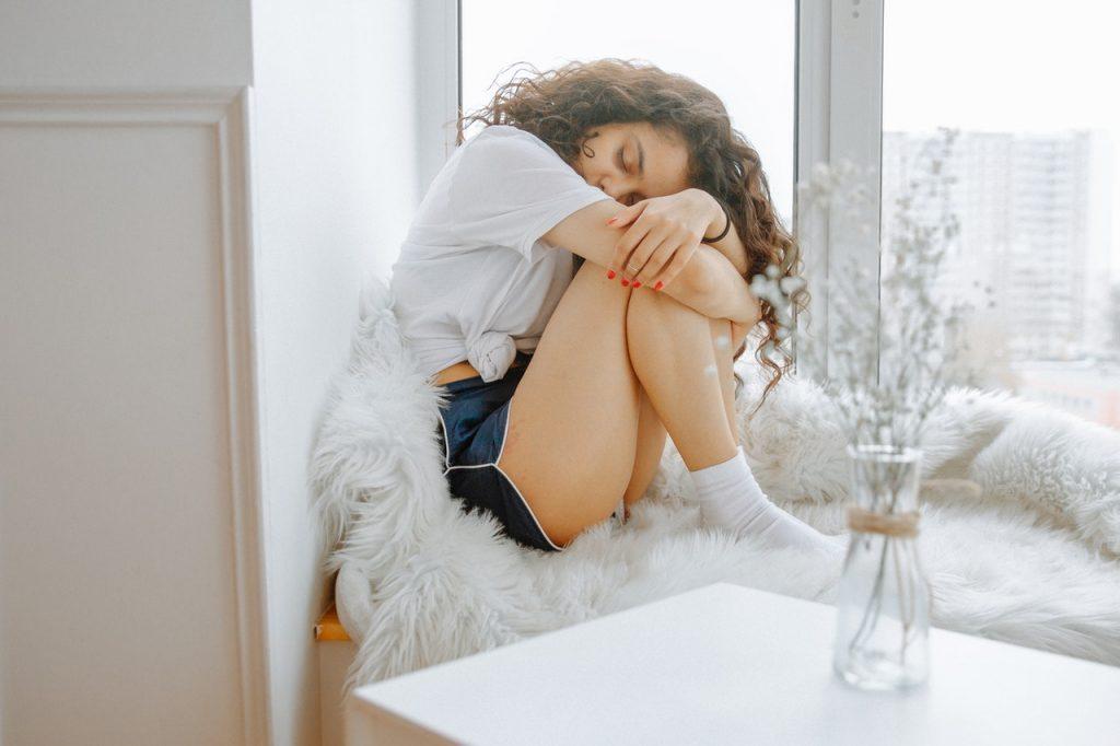 Mulher sentada em uma cadeira abraçando os joelhos.