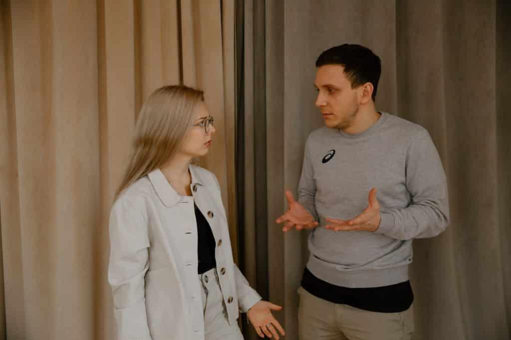 Homem e mulher discutindo e gesticulando com as mãos, lado a lado.