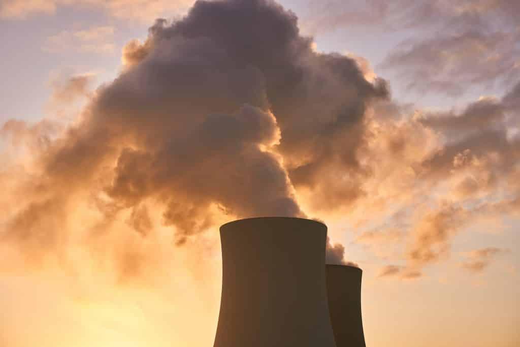 Chaminé industrial liberando fumaça no céu, ao fim da tarde.