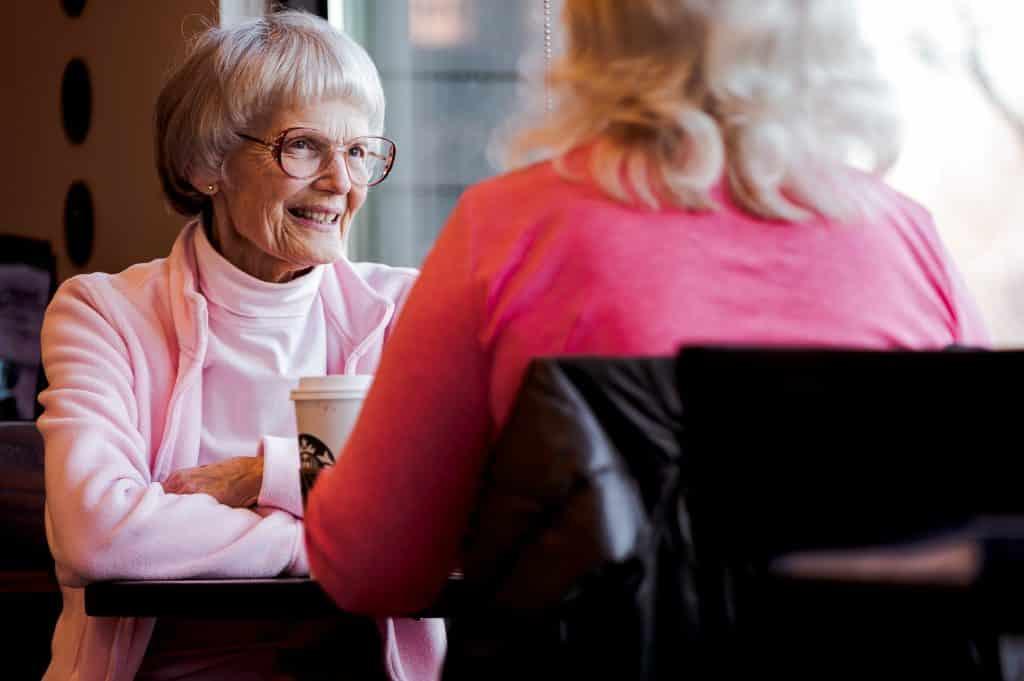 Duas mulheres idosas sentadas à mesa de um restaurante, sorrindo e conversando.