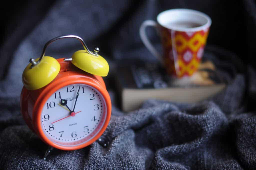 Relógio na cama ao lado de uma xícara de chá com um livro