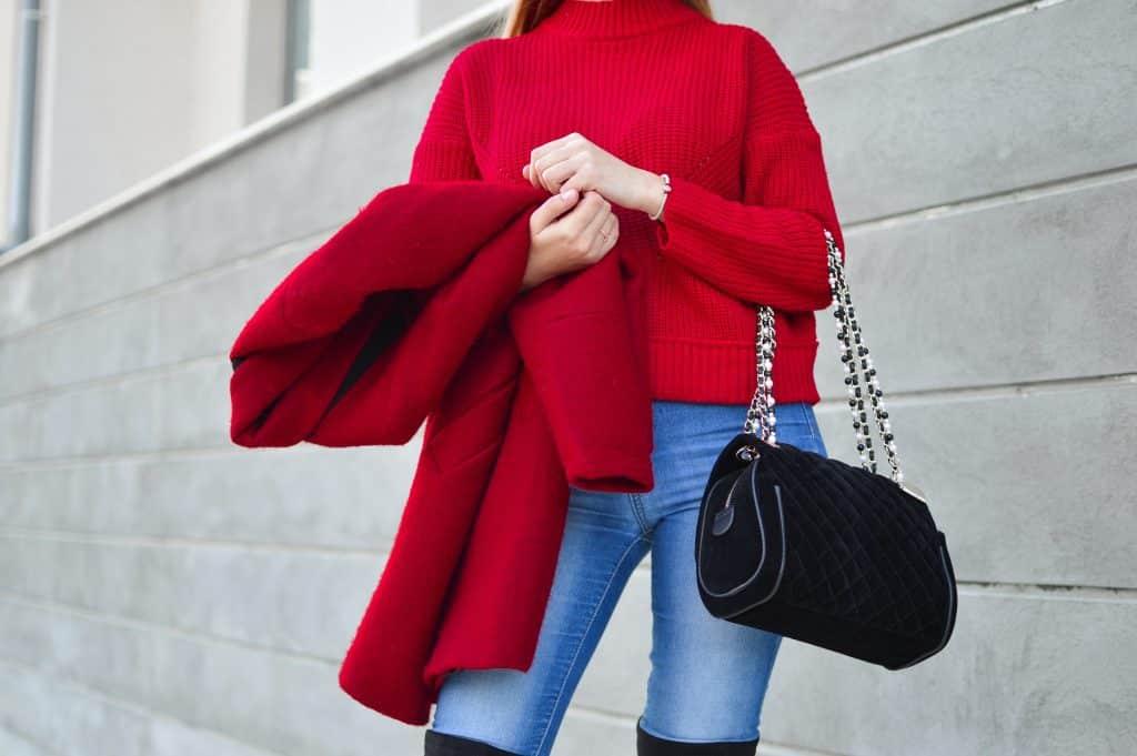 Mulher usando roupas vermelhas segurando uma bolsa com seu braço