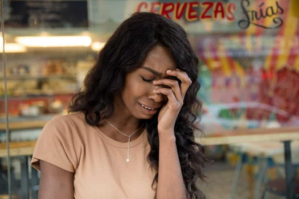 Mulher com a mão no rosto chorando