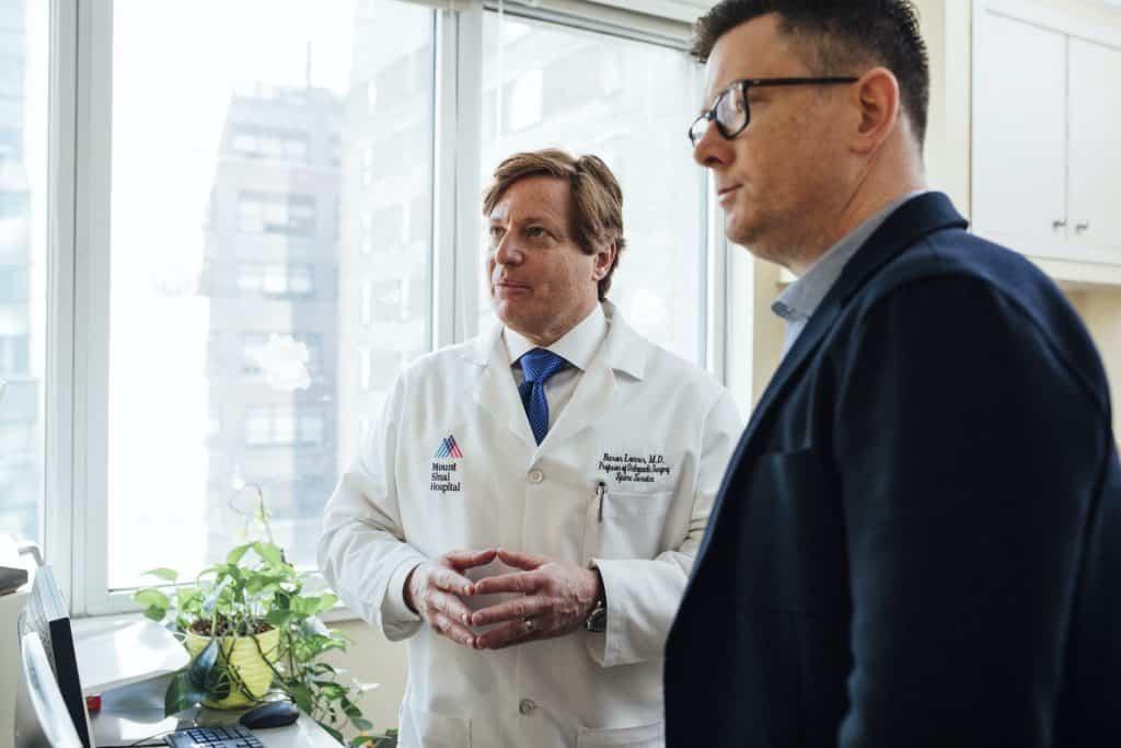 Médico de jaleco conversa com seu paciente, um homem adulto, em seu consultório.