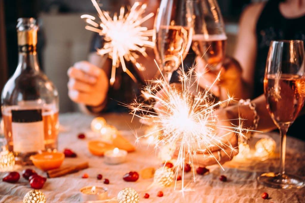 Pessoas ao redor da mesa com velas acesas e taças de champanhe