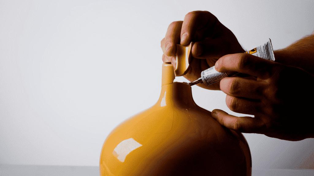 Pessoa colando cacos de vaso quebrado