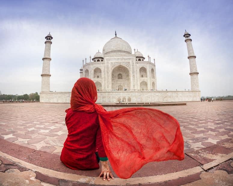 Mulher sentada de costas com Taj Mahal ao fundo