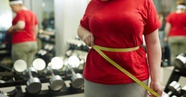 Mulher mede a cintura com fita métrica. O ambiente é de academia.
