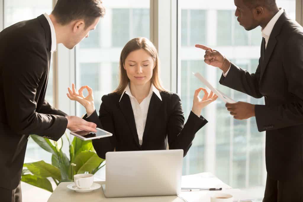 Mulher calma, meditando, enquanto dois homens gritam com ela em ambiente de trabalho