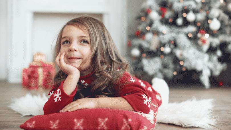 Menina deitada no chão com pijama de Natal. Ao fundo, decorações natalinas