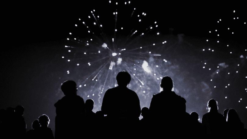 Pessoas olhando fogos de artifício no céu