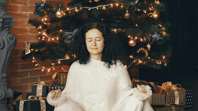 Mulher meditando embaixo da árvore de natal