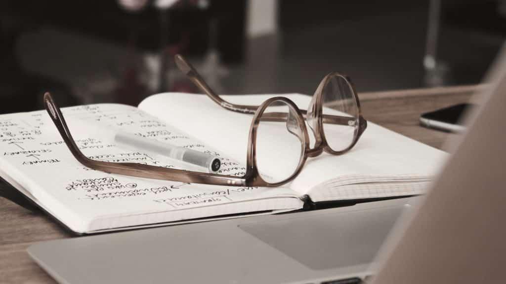 óculos aberto em uma agenda com anotações