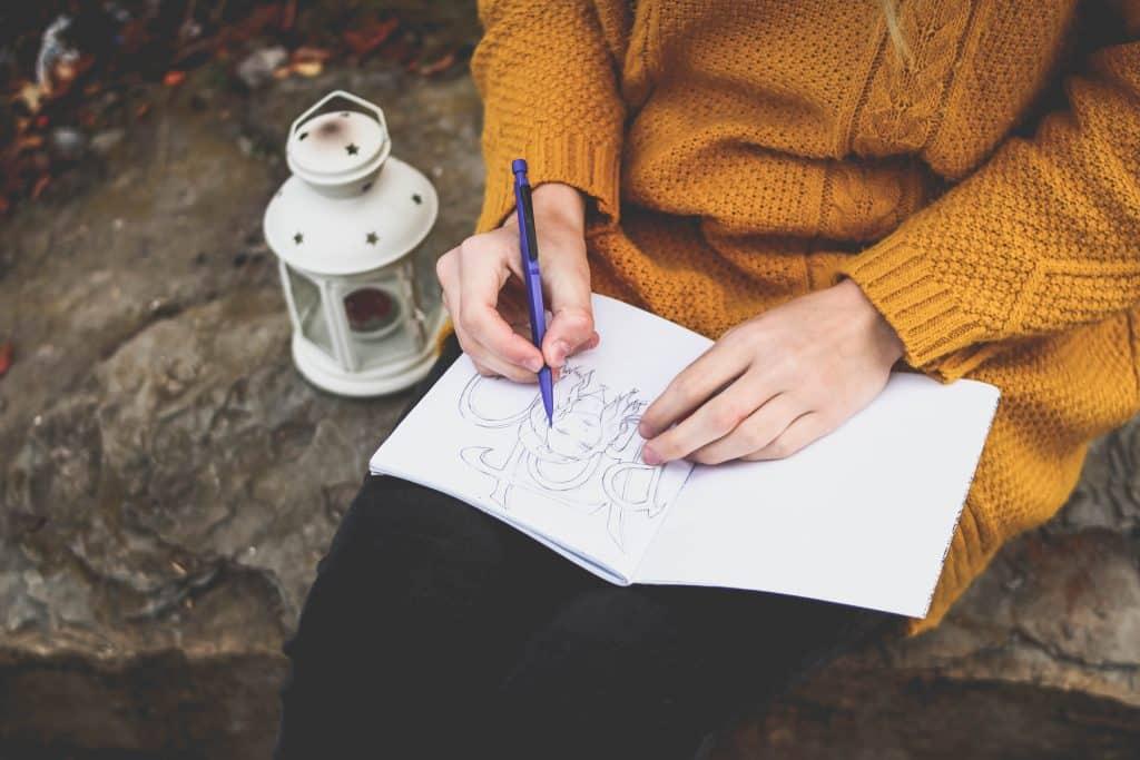 Mulher desenhando em um caderno