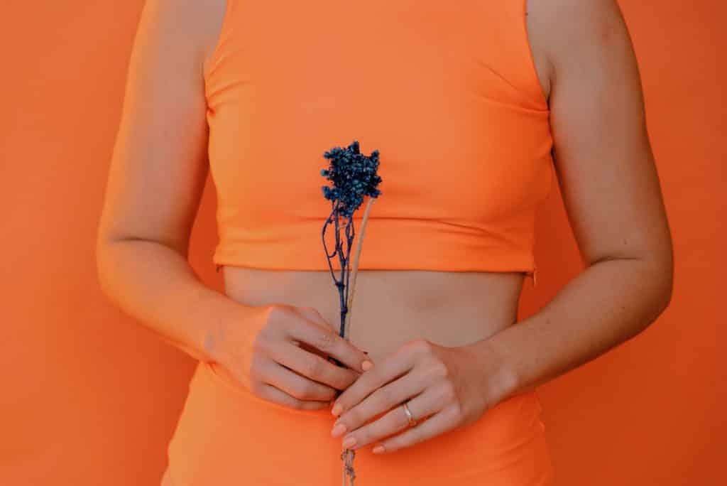 Mulher segurando uma flor e usando roupas laranjas