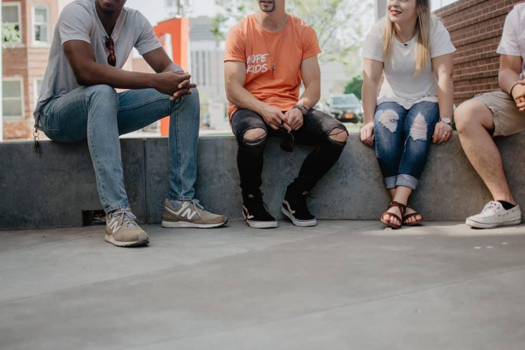 Pessoas sentadas na rua conversando