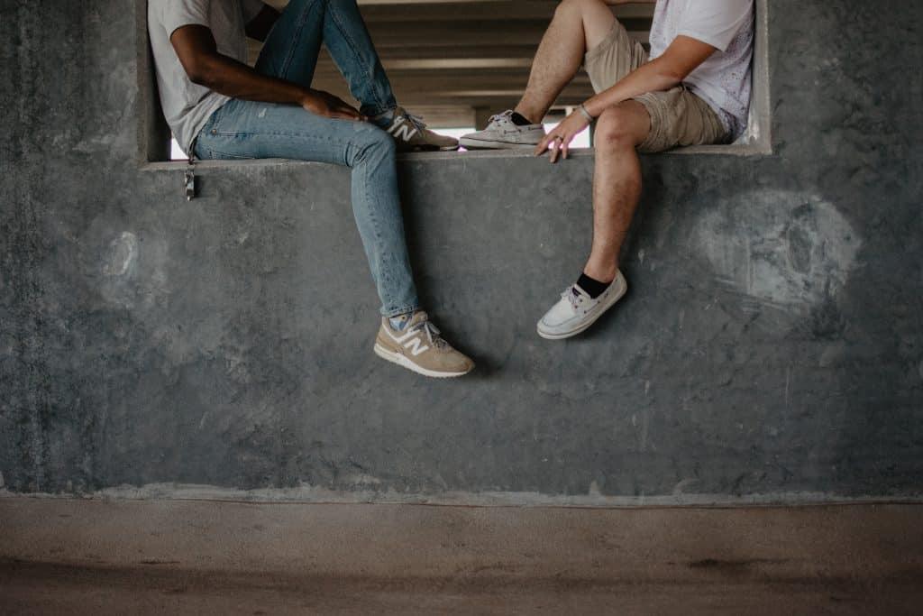 Duas pessoas sentadas em um muro de frente para o outro