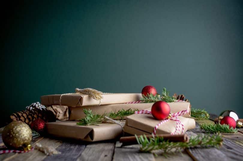 Presentes de Ntal embrulhados com papel e ao lado alguns enfeites