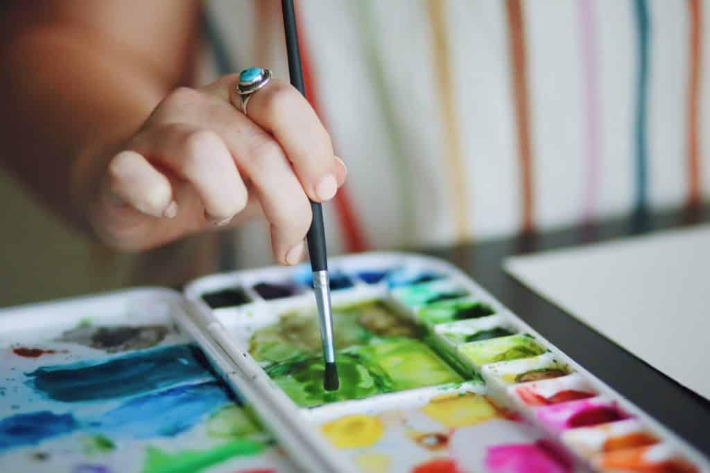 Mulher segurando pincel em direção a tinta