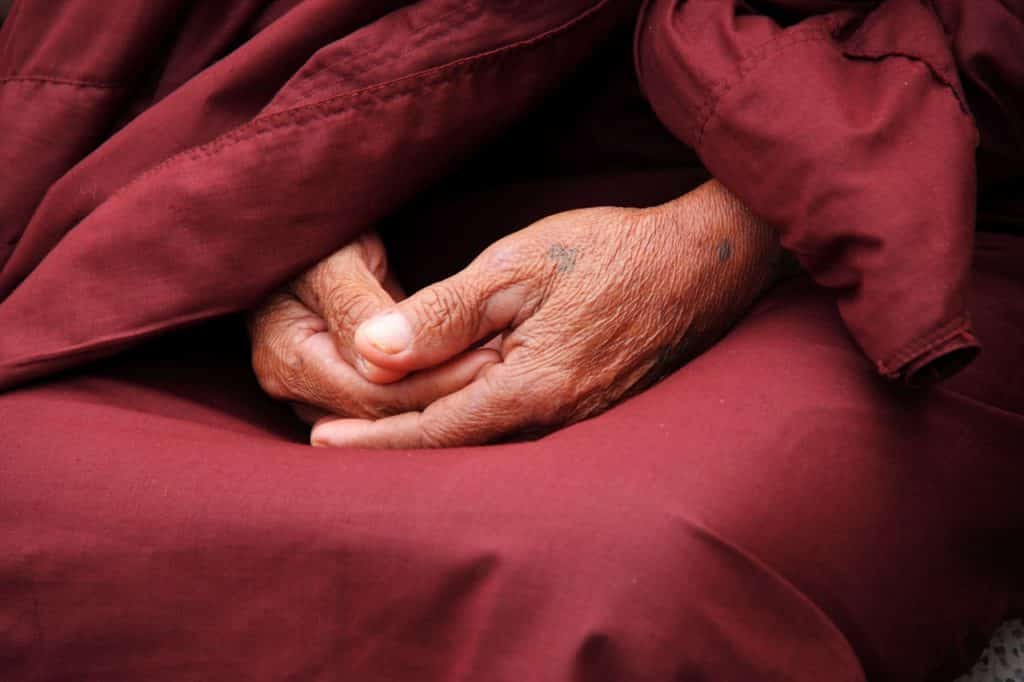 Mãos de uma pessoa sentada, que usa roupas budistas tradicionais.