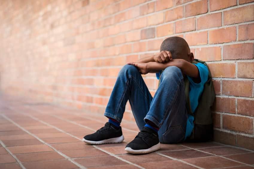 Menino sentado no chão, escondendo seu rosto com os braços.