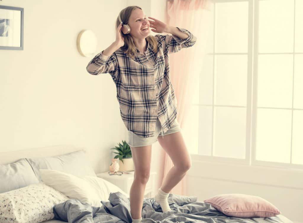 Mulher ouvindo música em pé na cama e sorrindo