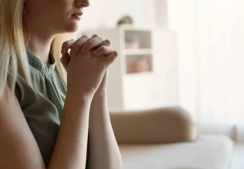 Mulher vista de perfil com as mãos unidas sobre o rosto, orando.