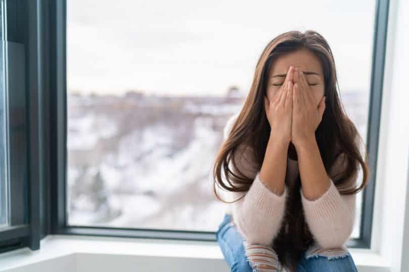 Mulher sentada na janela com maõs no rosto em sinal de nervosismo