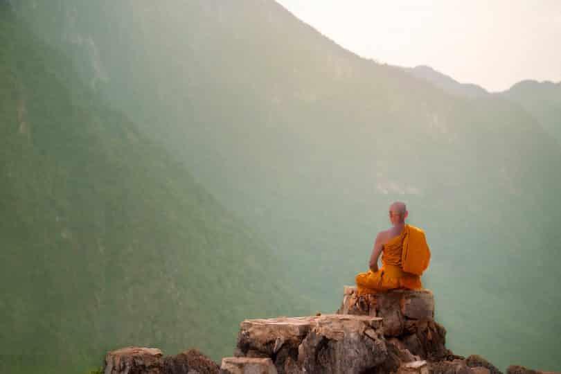 Monge budista meditando em uma montanha.