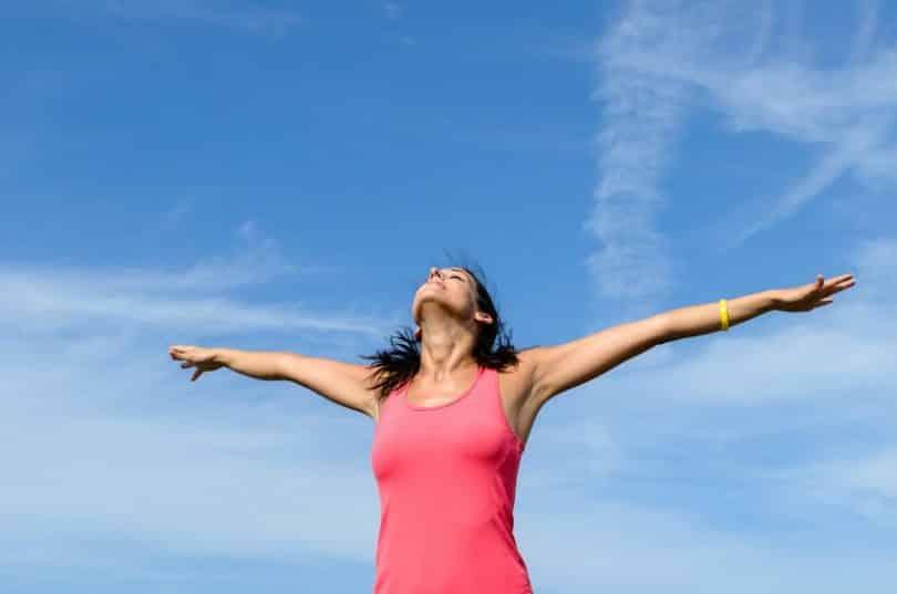 Mulher em pé com braços abertos vista de baixo com céu azul ao fundo