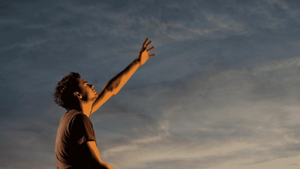 Homem com o braço erguido para o céu orando