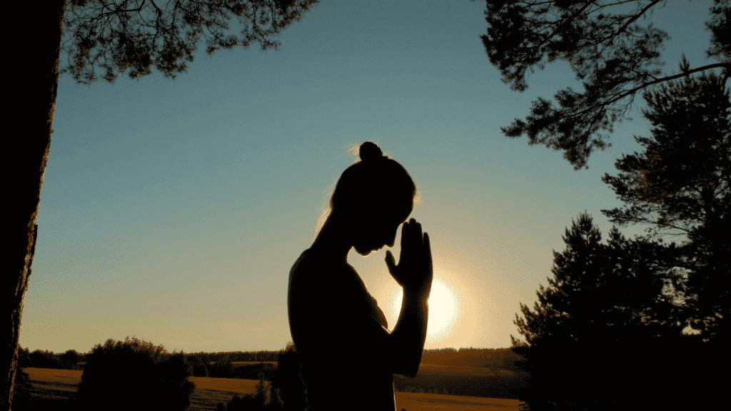 Silhueta de mulher orando sob por do sol