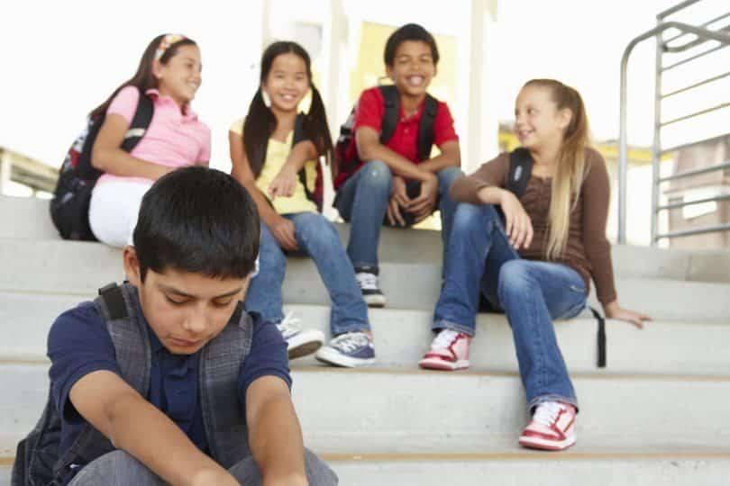 Menino sentado em uma escada sofrendo bulllying verbal de outras crianças da sua escola