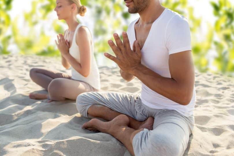 Duas pessoas sentadas na areia, de pernas cruzadas, meditando.