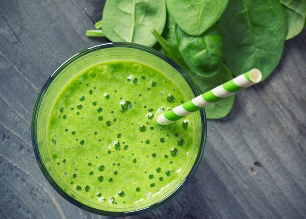 Vitamine verde com um canudo dentro do copo