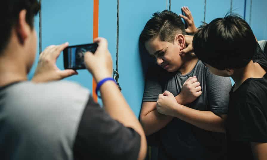 Menino sofrendo bullying enquanto outra criança filma com um celular.