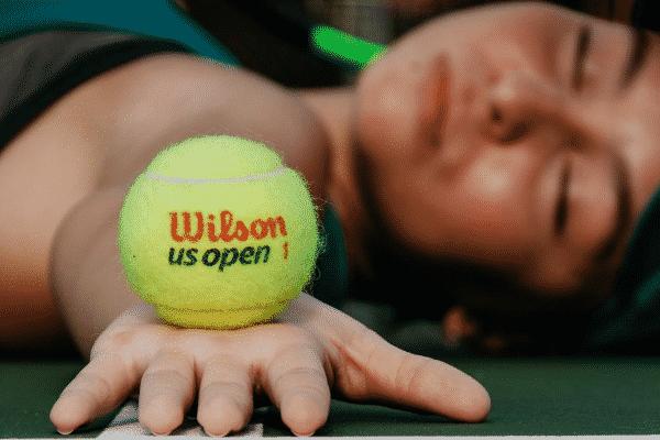 Mulher deitada no chão segurando bola de tênis