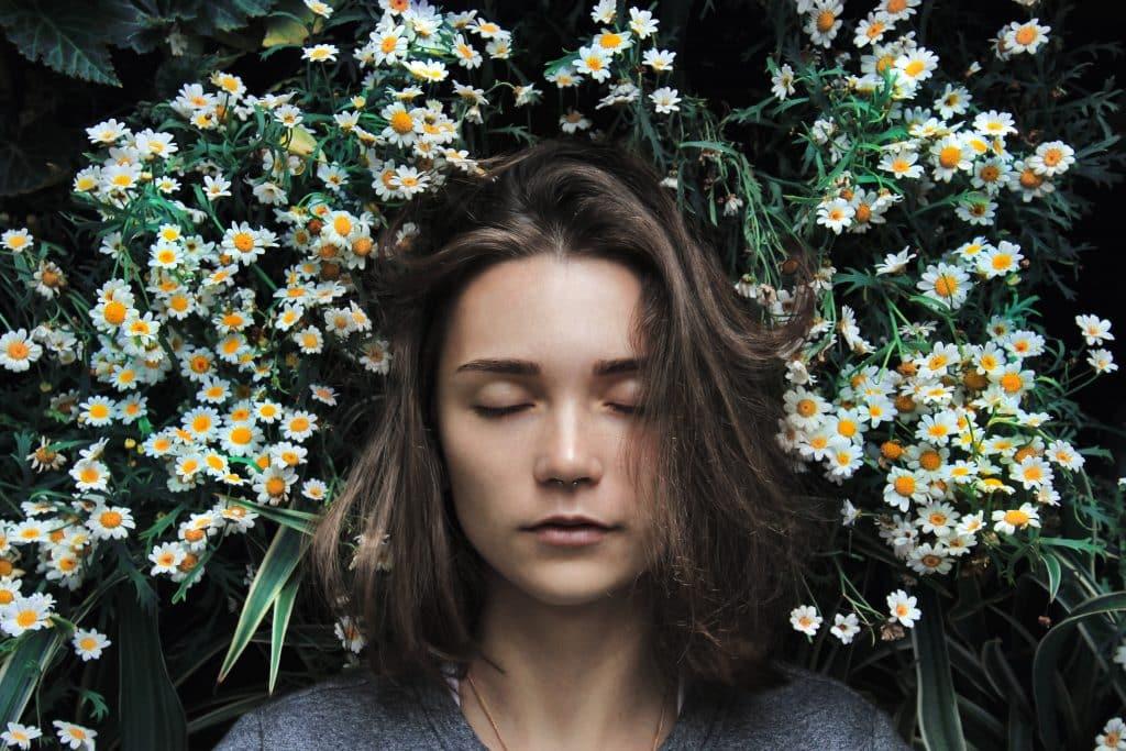 Mulher de olhos fechados em meio as flores de um jardim