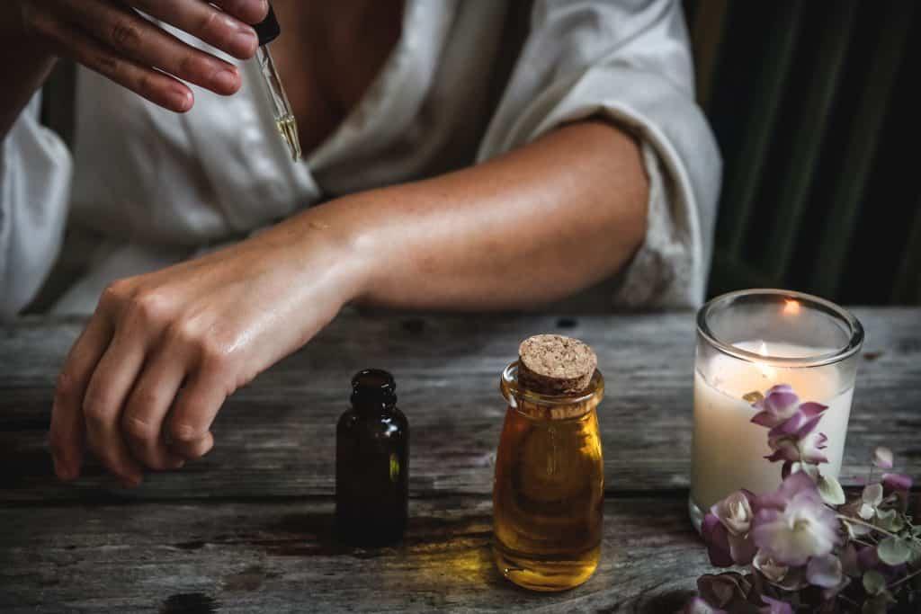 Mulher passando óleo em seu braço em cima da mesa com outras essências e uma vela